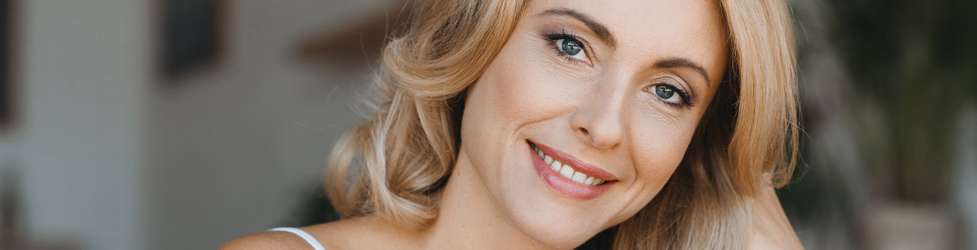 A woman is smiling after Jeuveau treatment